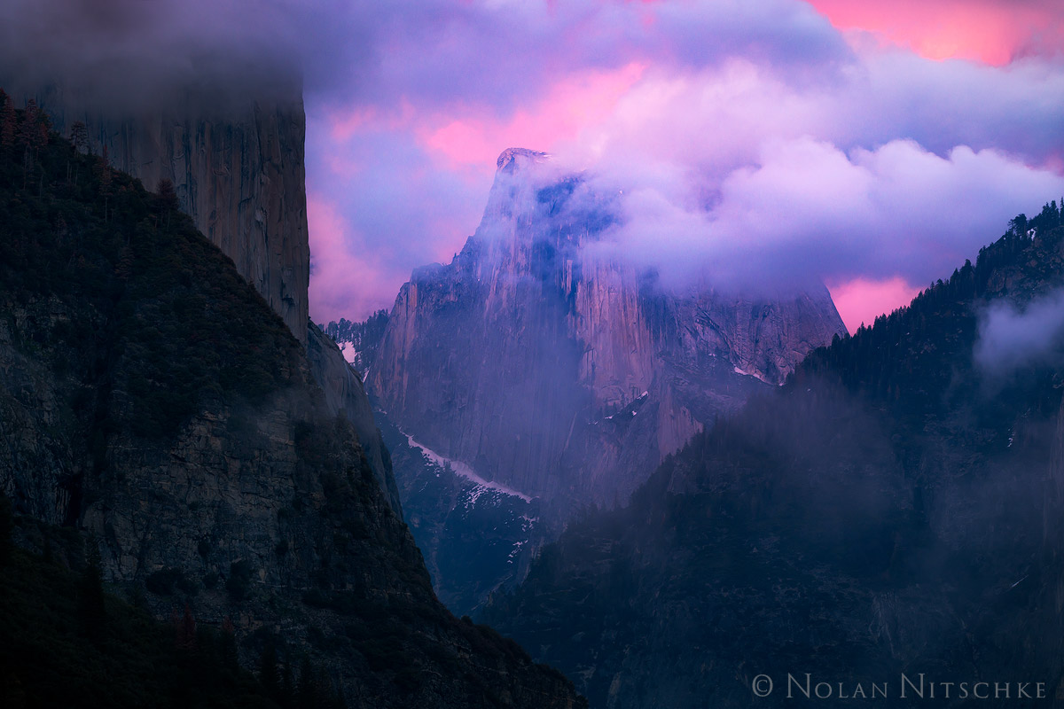 A clearing storm and pink glow illuminating Half Dome at sunset.