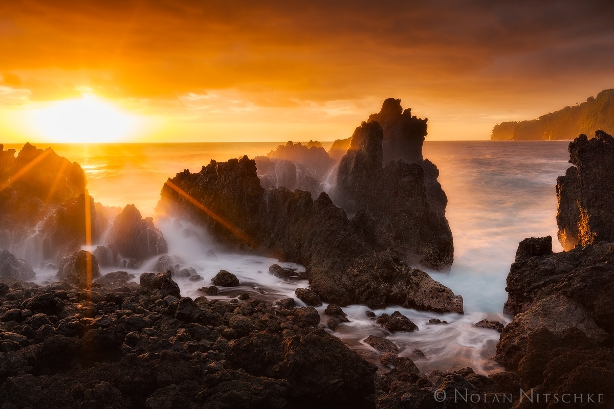 Waves crashing over jagged volcanic rock featuresalong the shore ofLaupāhoehoe Point at sunrise.