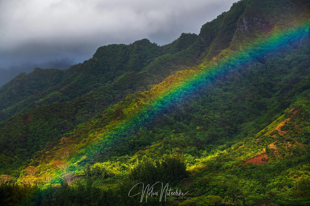 A rainbow forming over Kahana Bay.