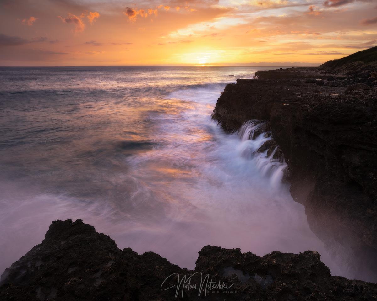 The setting sun and waves crashing again the coastline Ka'ena State Park.