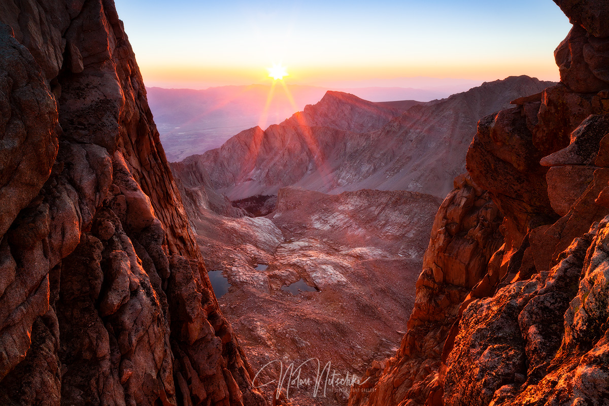 The sun rising between the Mt. Whitney Pinnacles  just before the summit in the Eastern Sierra Nevada. Here we are looking down...